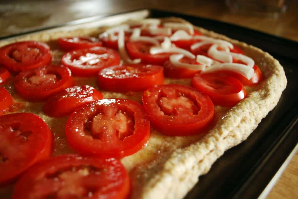 tomatoes and onions are neatly layered on top of a whole wheat pizza ...