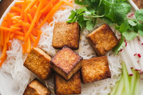 the best tofu recipe on a bed of noodles and salad