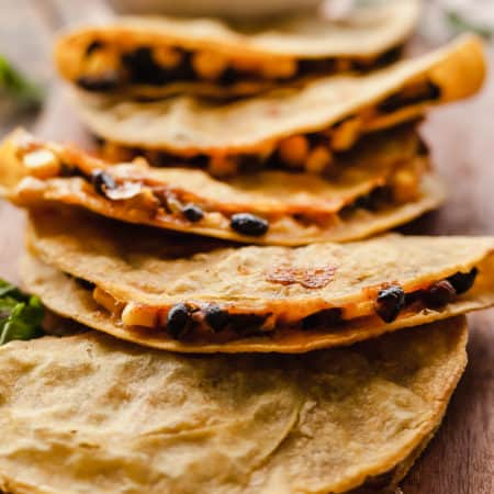 a line of crispy baked black bean tacos on a wood cutting board with a bowl of pico de gallo in the background