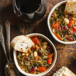 two bowls of Easy Minestrone Soup on a wood table with spoons, bread, and wine