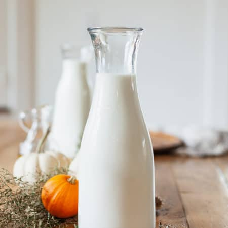 a carafe of milk on a wood table set with fall decor