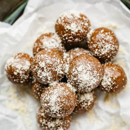 a pile of gingerbread energy balls on white parchment paper on a silver platter