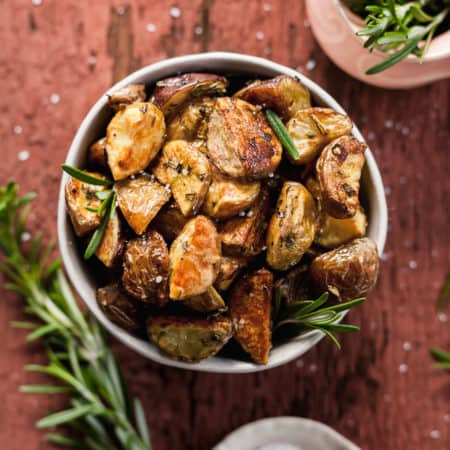 a bowl of oven roasted potatoes with rosemary on a red wood background with rosemary sprigs and salt