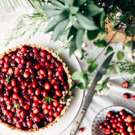 cranberry pie on a white table with green plants and a knife