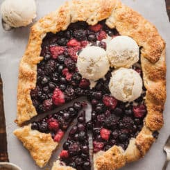 a mixed berry galette with two slices cut and a few scoops of vanilla ice cream