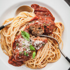 close up of eggplant meatballs cut open on spaghetti