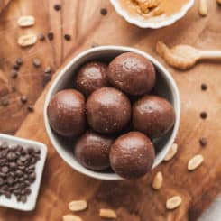 a small bowl of chocolate peanut butter protein balls with chocolate chips, peanuts, and peanut butter