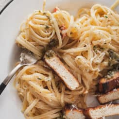 fettuccine alfredo twirled on a fork on a white plate with cajun tofu