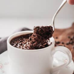 a hand taking a spoonful of microwave mug cake out of a white mug